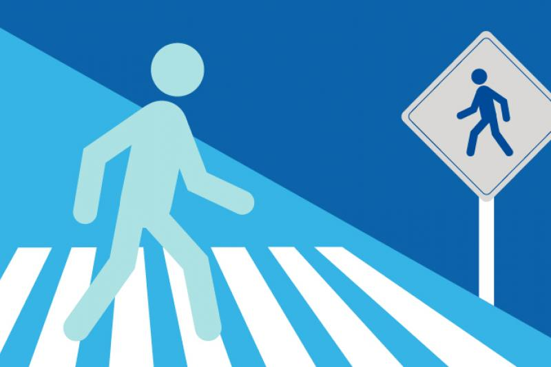 Decorative graphic of a person walking in a crosswalk