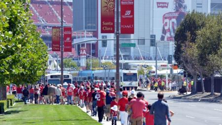 People walking with Levi's Stadium in the background