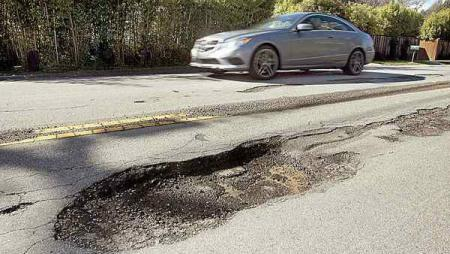 car driving by pot hole