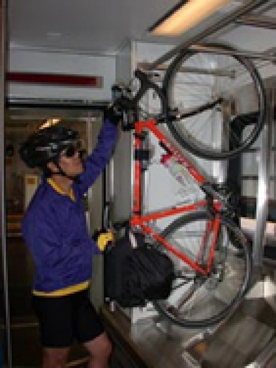 cyclist putting bike on light rail bike rack